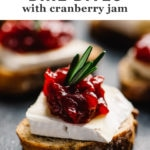 A cranberry brie bite - toasted baguette topped with a slice of brie cheese, cranberry jam, and rosemary garnish.