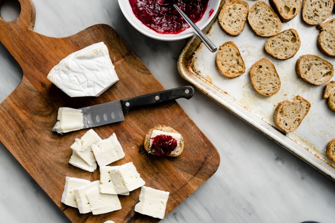 A bowl of cranberry jam, toasted crostini on a baking sheet, and slices of brie cheese on a cutting board with one composed cranberry brie bite.