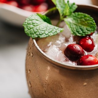 A close up image of a cranberry moscow mule cocktail garnished with mint, fresh cranberries, and a lime wedge.
