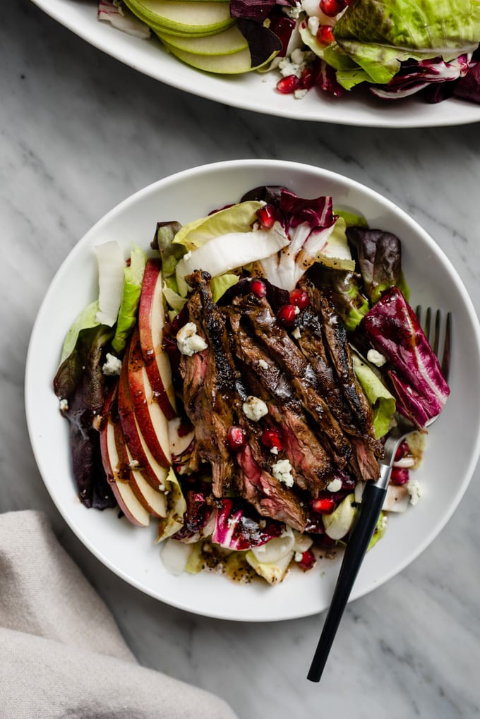 Winter chopped salad with pear, endive, and arugula topped with seared steak in a white bowl.
