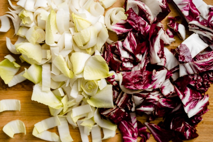 Chopped endive and radicchio on a cutting board.