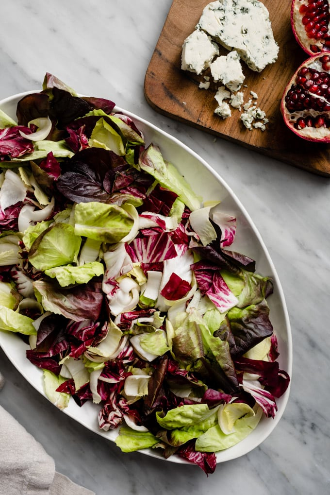 Winter chopped salad base of endive, radicchio, and butter lettuce on a platter.