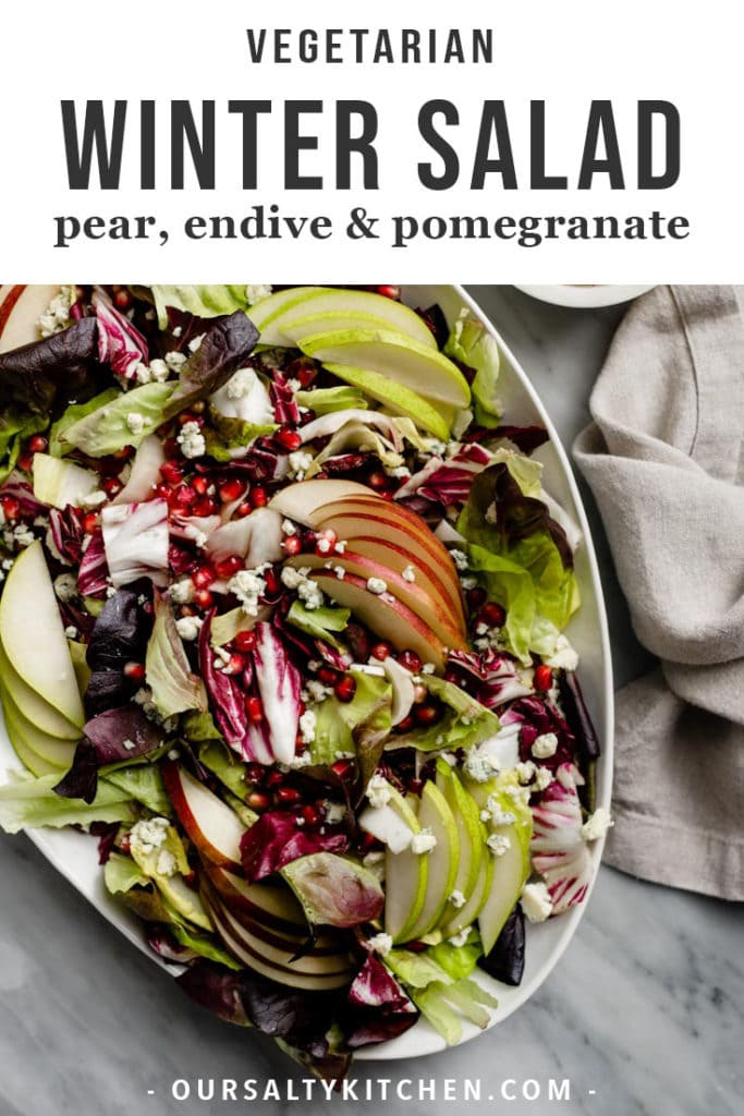 Winter chopped salad on a platter with endive, radicchio, butter lettuce, pear, pomegranate, and blue cheese, with a small bowl of pomegranate vinaigrette.
