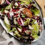 Winter chopped salad with endive, pear, blue cheese, and pomegranate on a white platter.