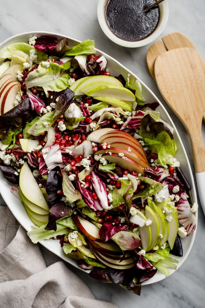 Winter chopped salad with endive, pear, and pomegranate on a white platter with a bowl of pomegranate vinaigrette on a marble table.