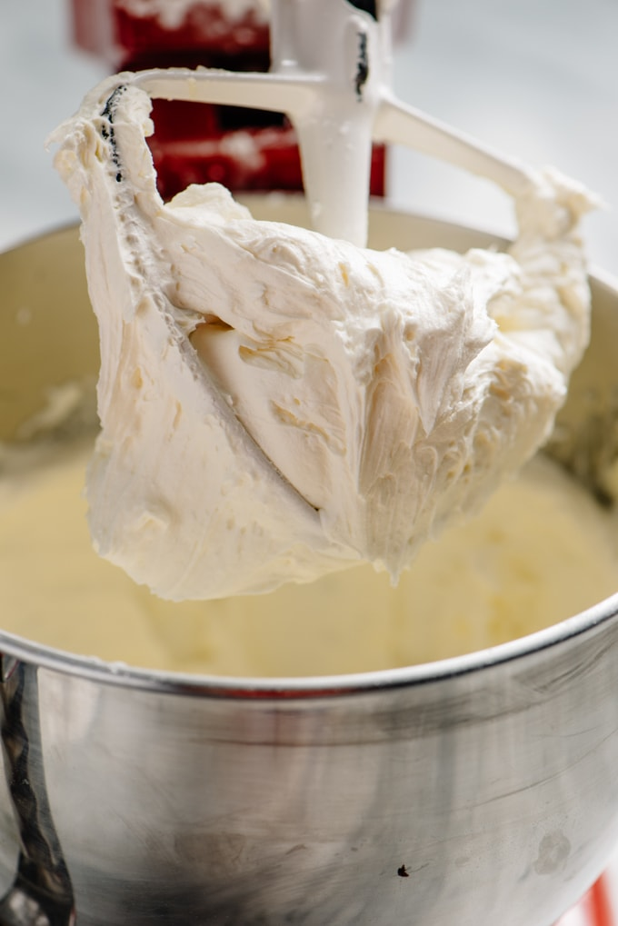 Peppermint buttercream frosting on the paddle attachment of a mixing bowl.