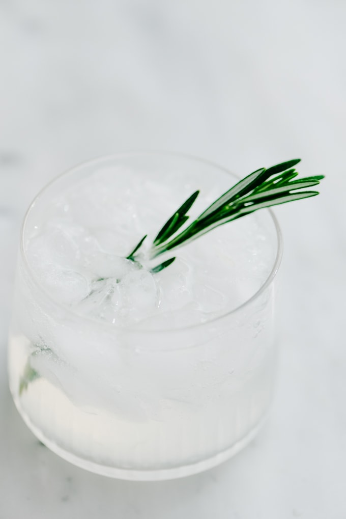 A rosemary vodka gimlet on the rocks topped with soda water and garnished with a fresh rosemary sprig.