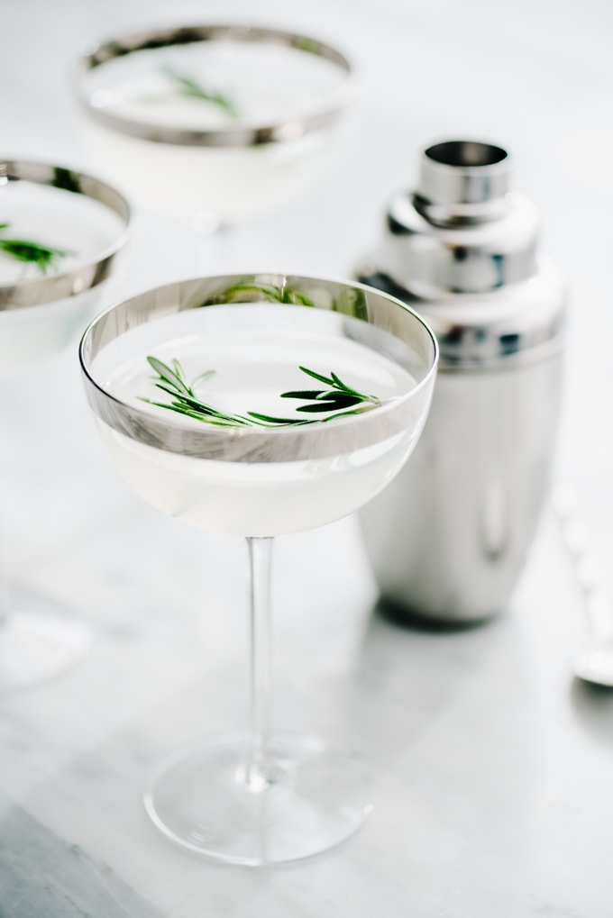 Several vodka gimlet cocktails with rosemary simple syrup in coupe glasses on a marble table with a silver cocktail shaker.
