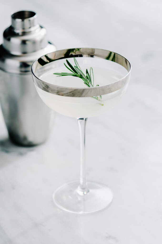 A rosemary infused vodka gimlet served in a couple glass with a silver rim on a marble table with a cocktail shaker in the background.