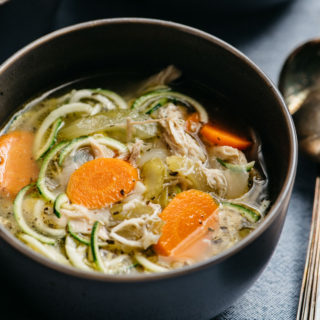 A bowl of low carb and Whole30 chicken zoodle soup on a blue tablecloth with soup spoons.