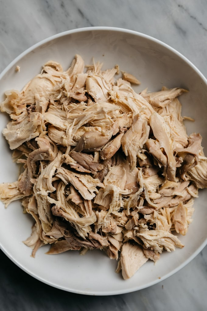 A bowl of shredded poached chicken for making homemade chicken zoodle soup with bone broth.