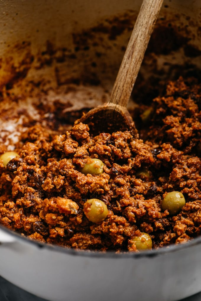 A close-up image of cuban picadillo with green olives in a dutch oven.