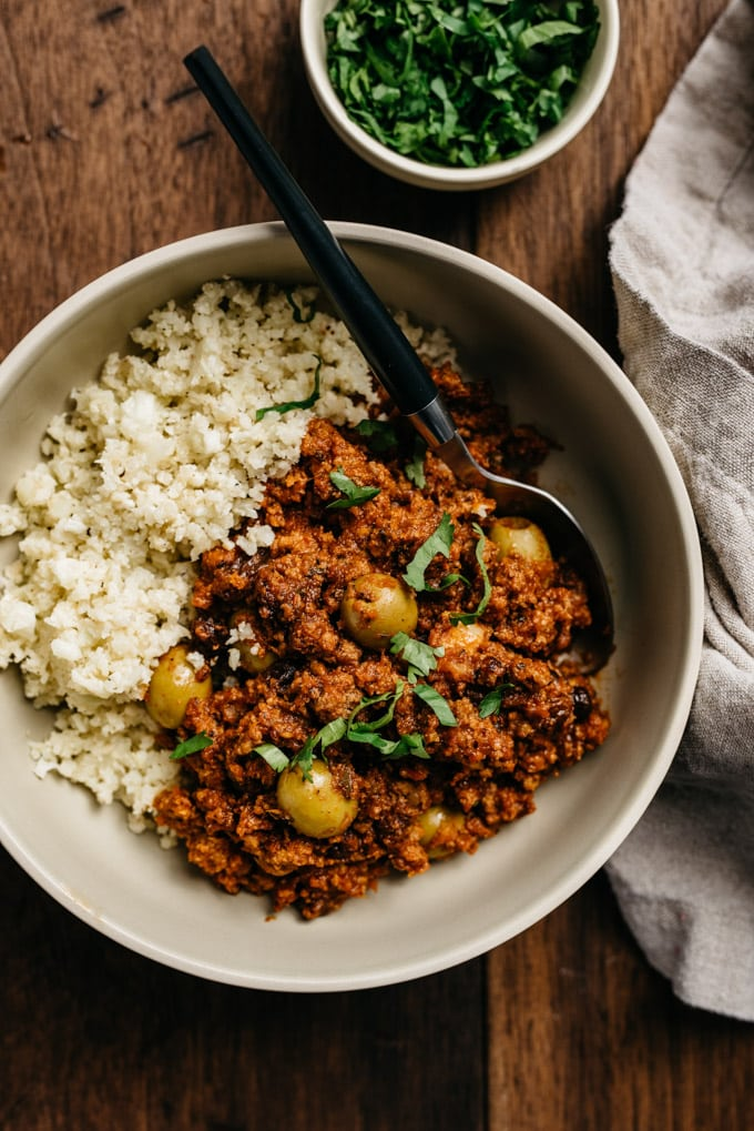 A low carb and Whole30 picadillo recipe served over cauliflower rice garnished with cilantro in a tan bowl.