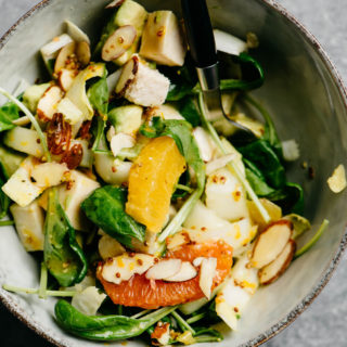 A bowl of Whole30 orange chicken salad with endive, almonds, avocado, and citrus vinaigrette on a cement background.