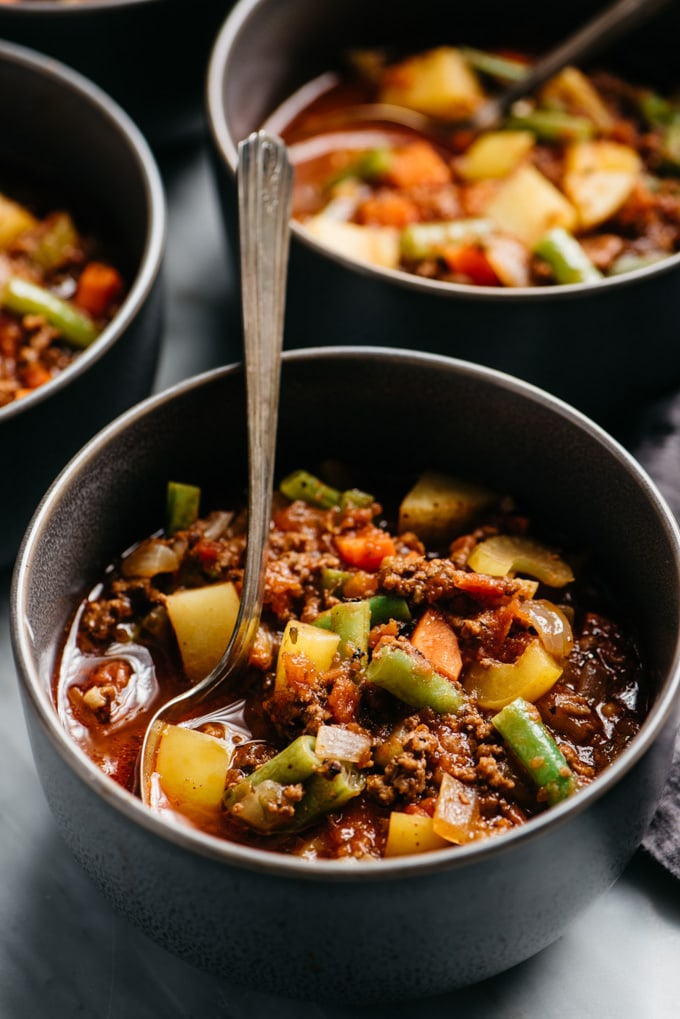 A bowl of paleo and whole30 hamburger soup in a grey bowl with a silver soup soon.