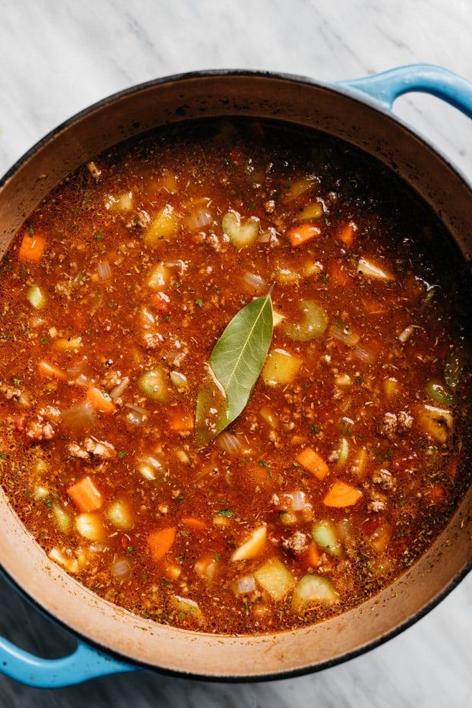 Hamburger soup ingredients in a dutch oven with a bay leaf before being simmered.