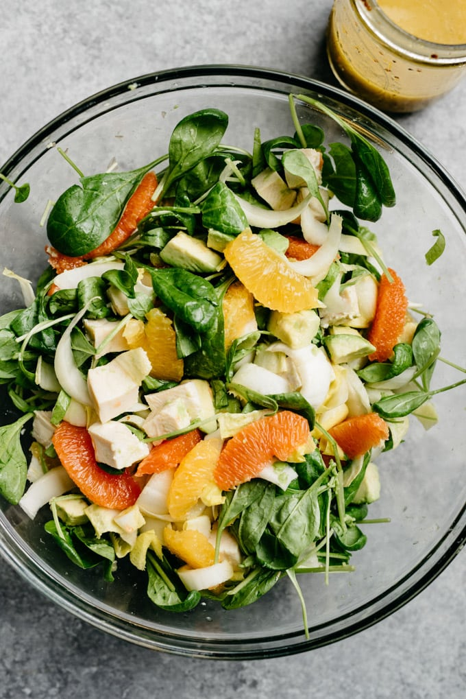 Orange chicken salad tossed in a large glass mixing bowl.