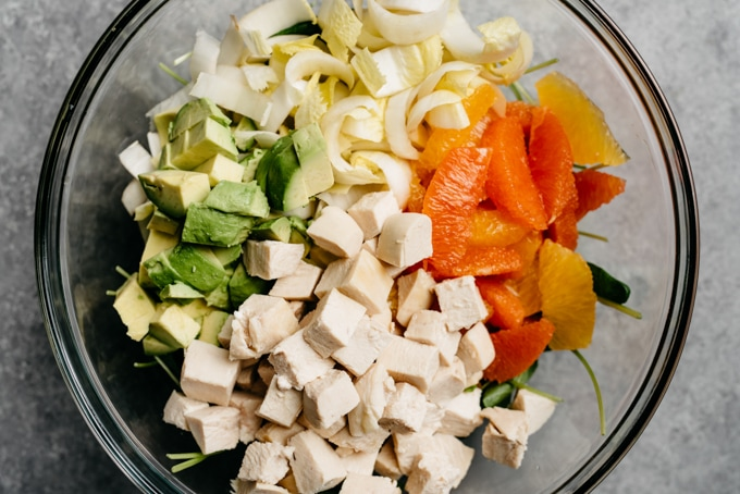 A glass mixing bowl with poached chicken, citrus supremes, endive, avocado, and spinach for making orange chicken meal prep bowl.