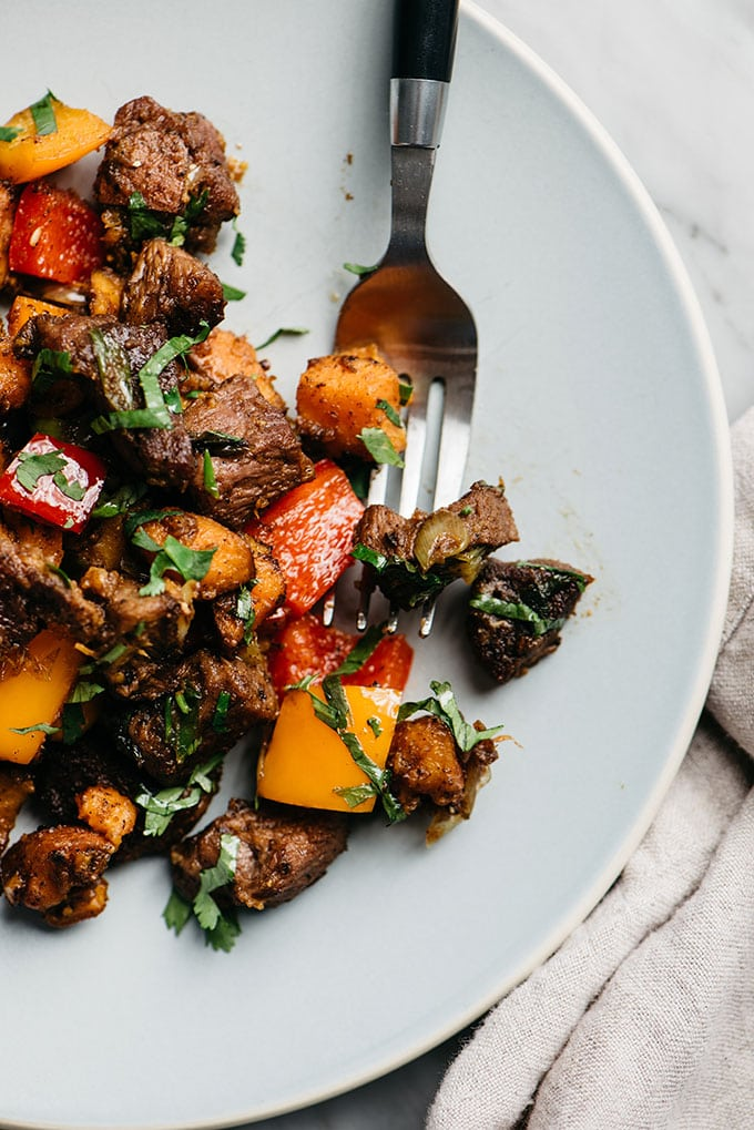 A close-up image of a forkful of Whole30 steak bites with sweet potatoes, bell peppers, cilantro, and green onions.