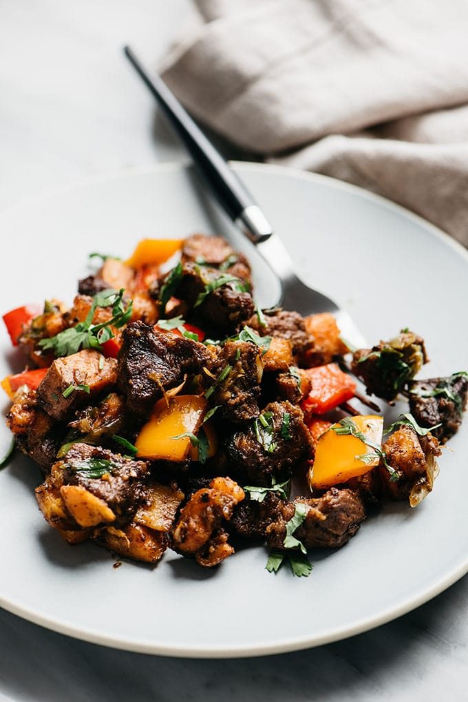A serving of Whole30 steak bites with sweet potatoes, bell peppers, green onions, and cilantro on a blue plate.