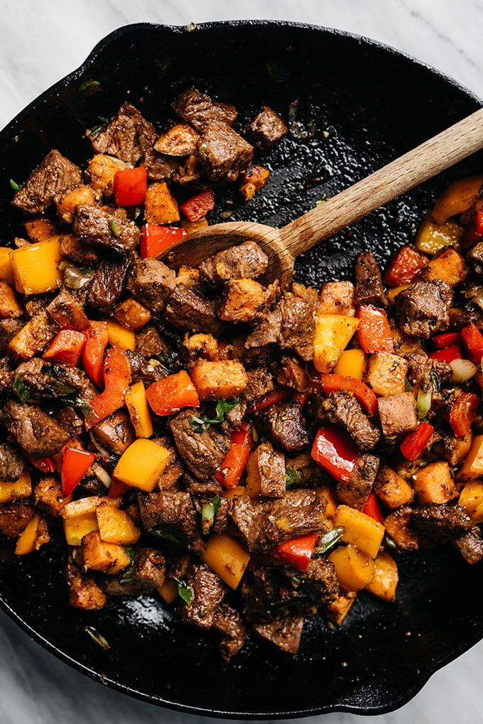 Whole30 steak bites with sweet potatoes and peppers in a cast iron skillet.