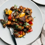 Whole30 steak bites sauteed with sweet potatoes and bell peppers on a blue plate with a black fork.