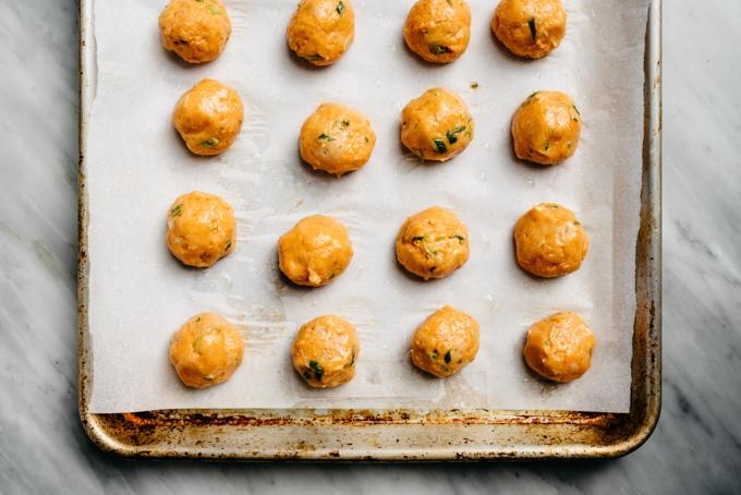 Formed raw gluten free buffalo chicken meatballs on a baking sheet.