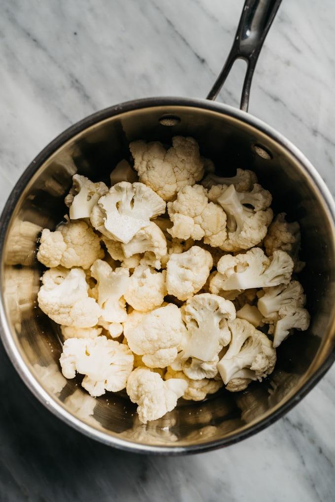 Cauliflower florets in a medium sauce pot with chicken broth for making cauliflower puree.