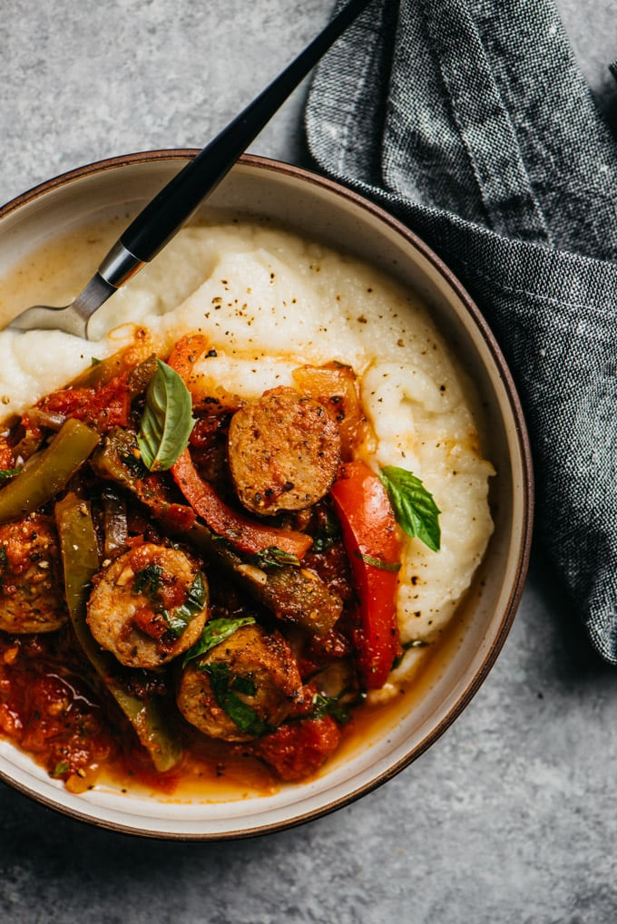 A bowl of healthy italian sausage and peppers over gluten free cauliflower puree on a cement background with a grey linen napkin.