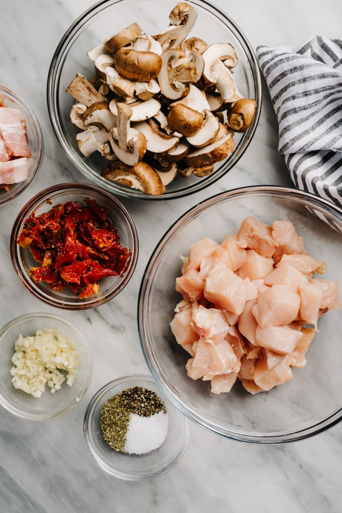 The ingredients for healthy tuscan chicken bites in bowls on a marble table.