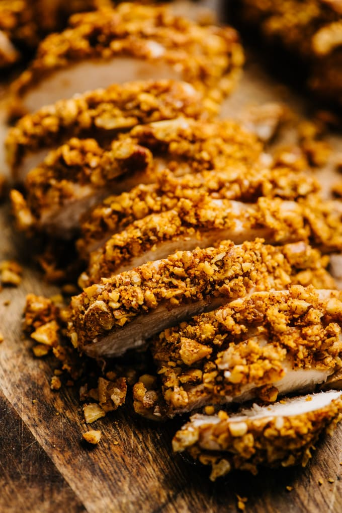 Baked pecan chicken breasts thinly sliced on a cutting board.