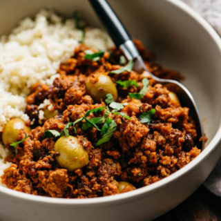 A low carb and Whole30 picadillo recipe served over cauliflower rice in a tan bowl.