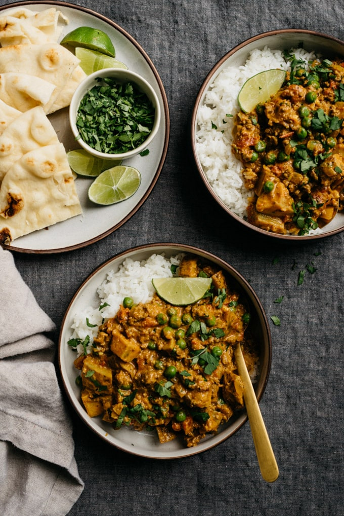 Two bowls of keema curry prepared with peas and potatoes, and served over white rice, on a table with a side plate of naan.