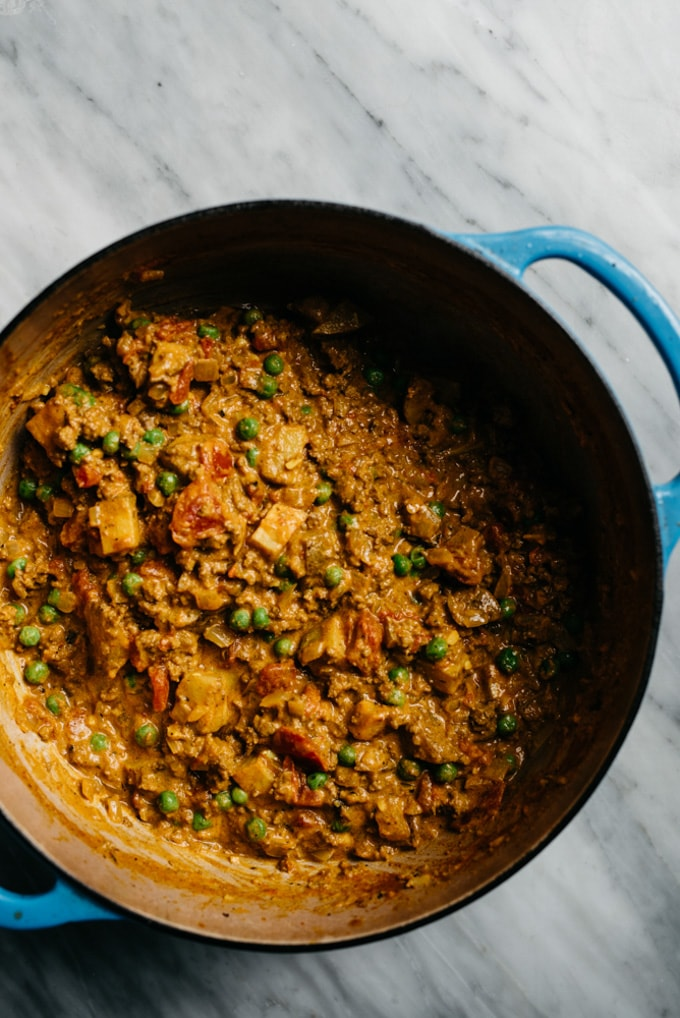 Cooked keema curry with peas and potatoes in a blue dutch oven.