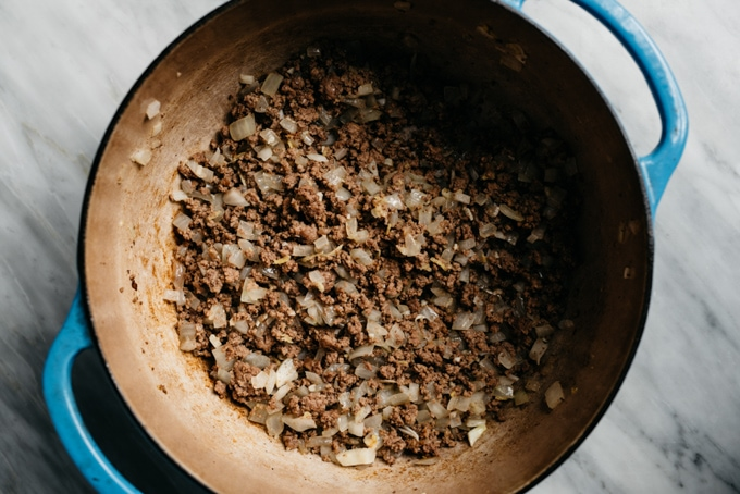Ground beef sauteed with onions, garlic and ginger in a dutch oven, forming the base for keema curry.