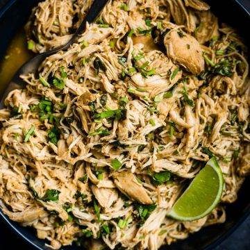 A serving bowl of Whole30 chicken lime chicken with a lime wedge and serving spoon.