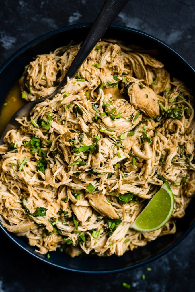 A serving bowl of Whole30 cilantro lime chicken with a lime wedge and serving spoon.