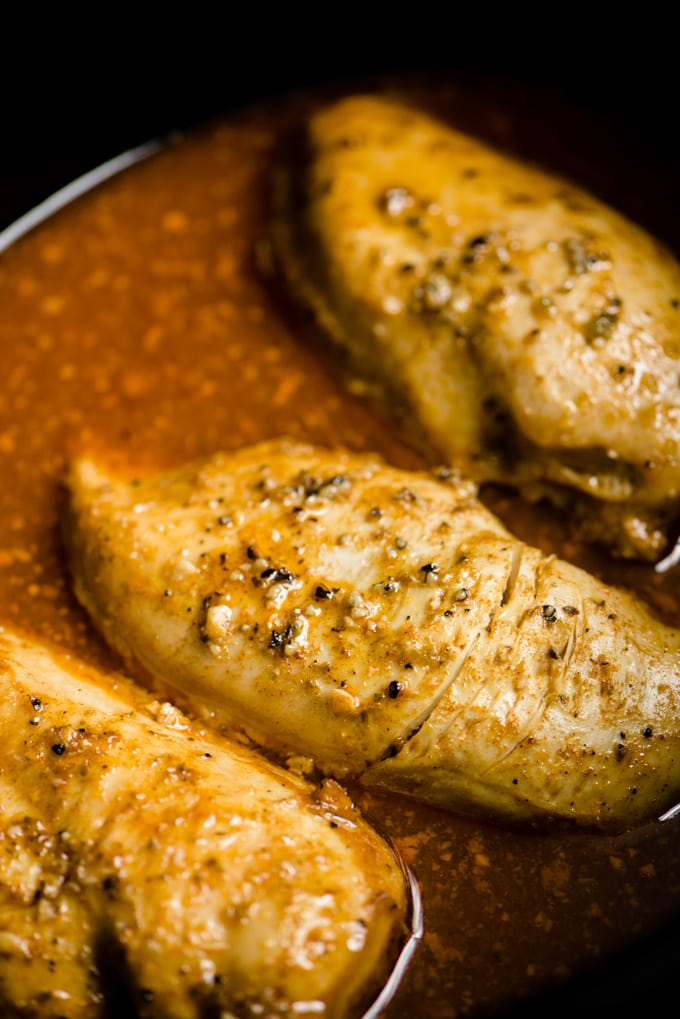 Cooked chicken breasts in a crock pot covered in cilantro lime sauce.