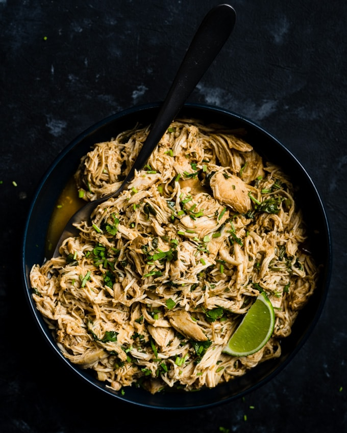 A bowl of keto and low carb cilantro lime chicken cooked in a crock pot, garnished with a lime wedge.