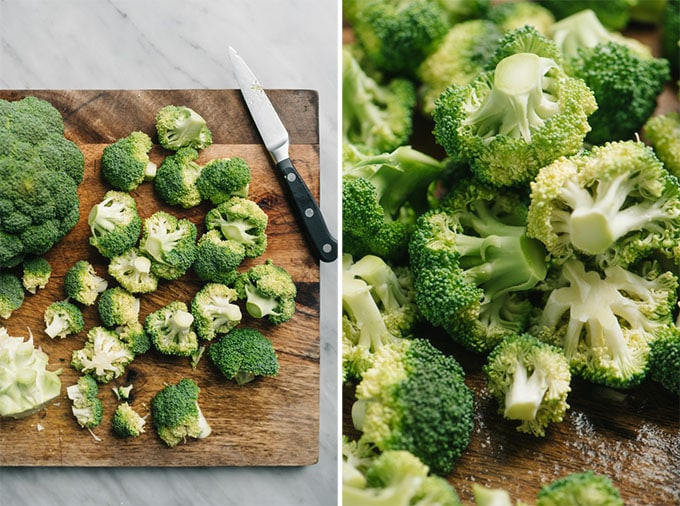 Chopped bite-sized broccoli florets on a cutting board.