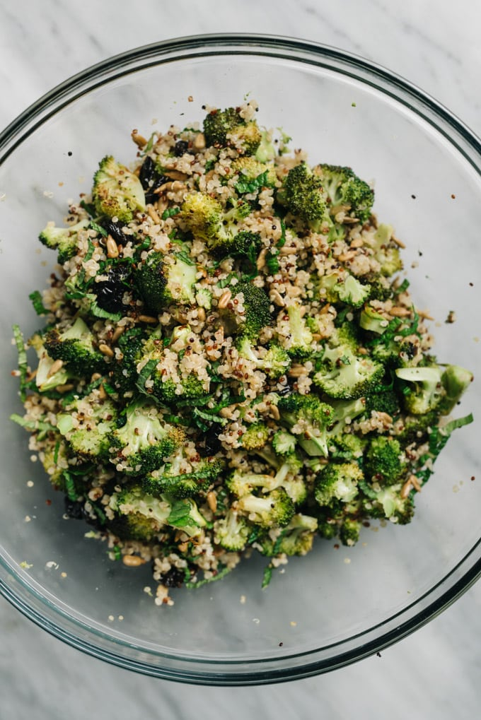 Vegan broccoli quinoa salad tossed in a glass mixing bowl.