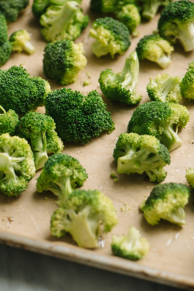Bite sized broccoli florets on a baking sheet tossed with olive oil, salt, and pepper.