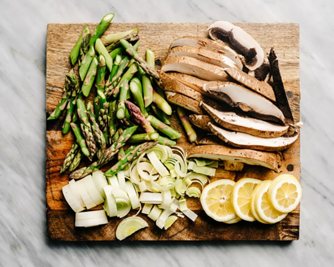Chopped asparagus, sliced mushrooms, sliced leeks, and lemon wheels on a cutting board.