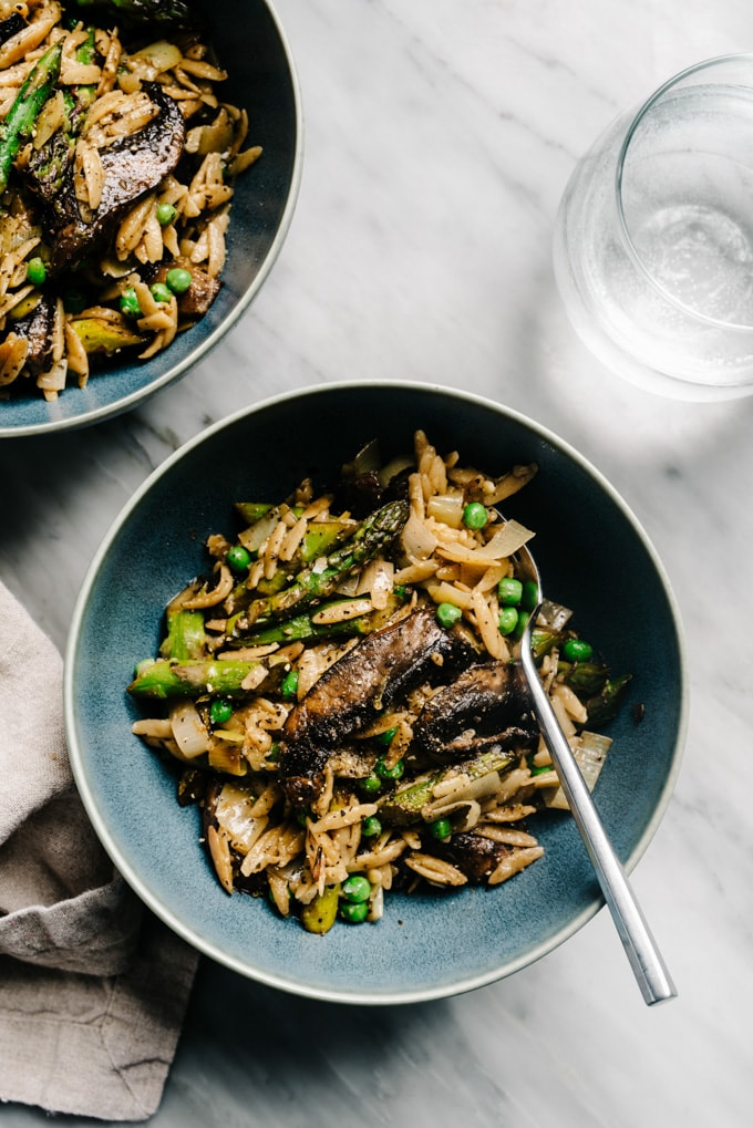 Two bowls of vegan lemon orzo pasta with asparagus, mushrooms, and peas on a marble table.