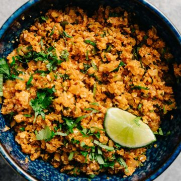 A bowl of mexican cauliflower rice with cilantro and a lime wedge.