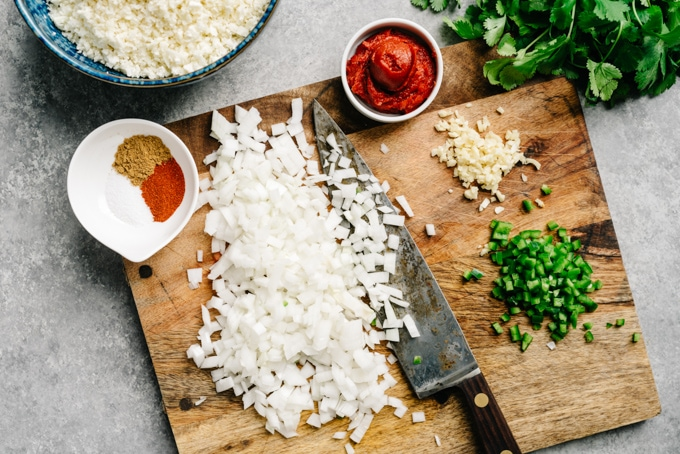 Ingredients for mexican cauliflower rice arranged on a cutting board atop of cement table.