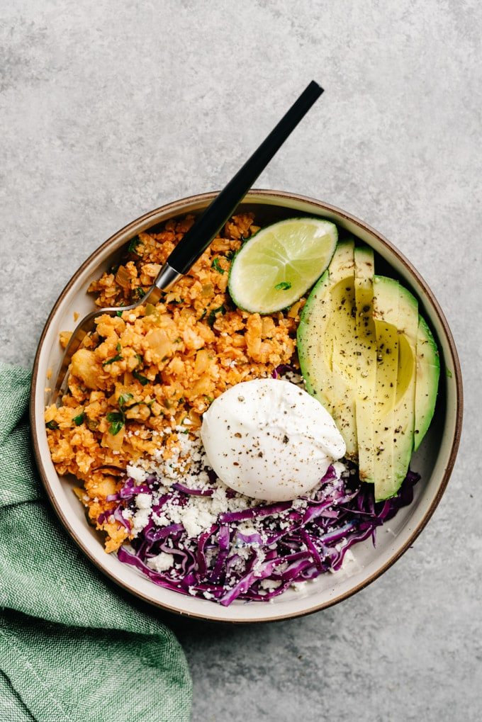Mexican cauliflower rice keto bowl with avocado, poached egg, cabbage, and queso fresco.
