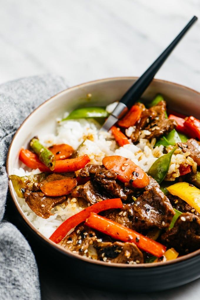 A bowl of gluten free stir fry steak served over rice.