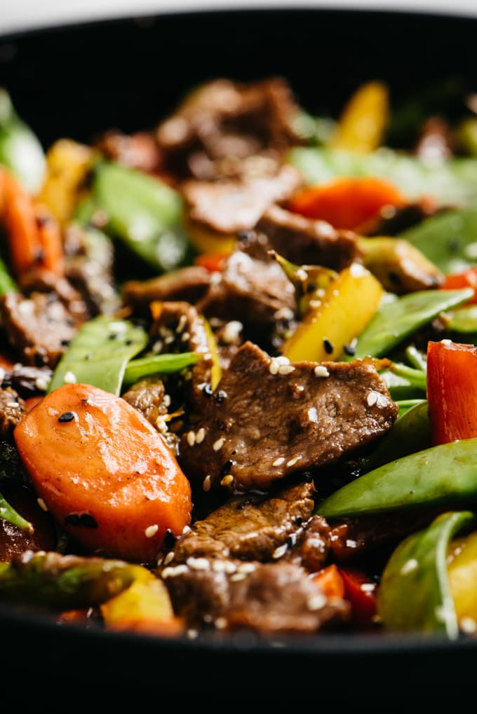 Paleo stir fry steak with rainbow vegetables, gluten free sauce, and sesame seeds.