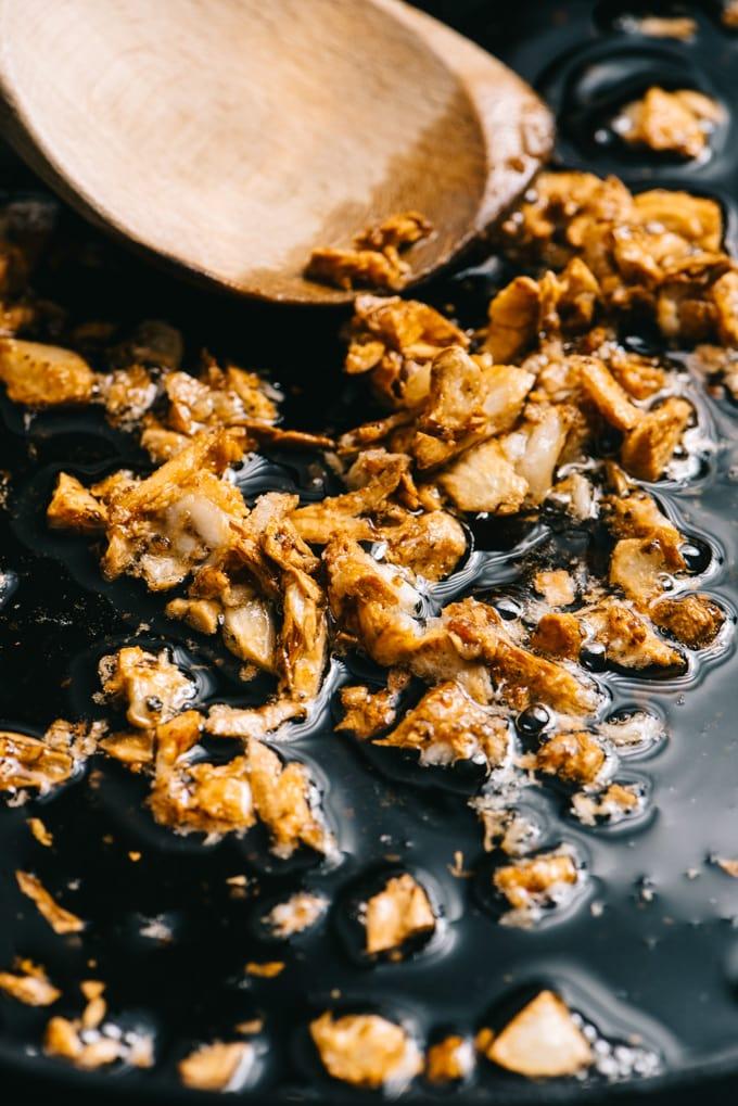 Golden brown crushed garlic in a skillet.